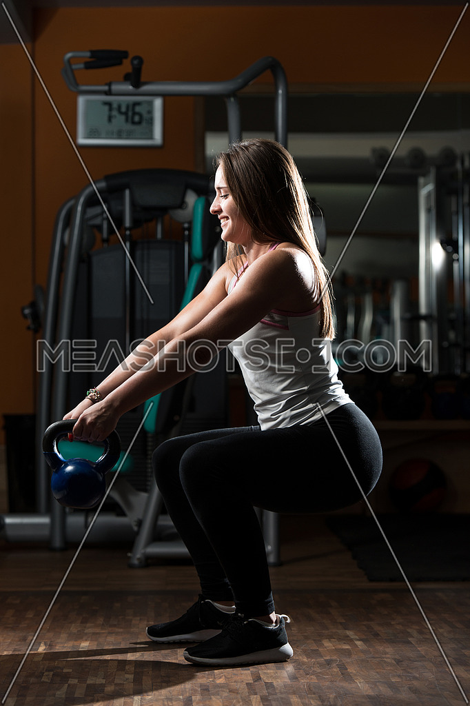 Young Woman Working Out With Kettle Bell