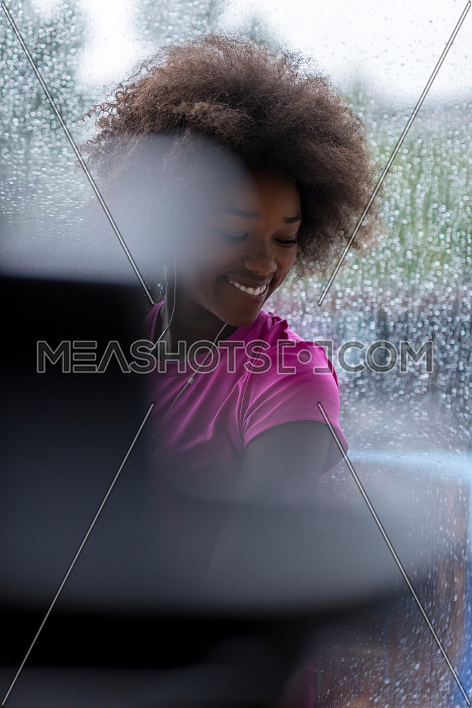 portrait of young afro american woman in gym on work out break while teaking breath and fresh water rainy day and bad weather outdooor