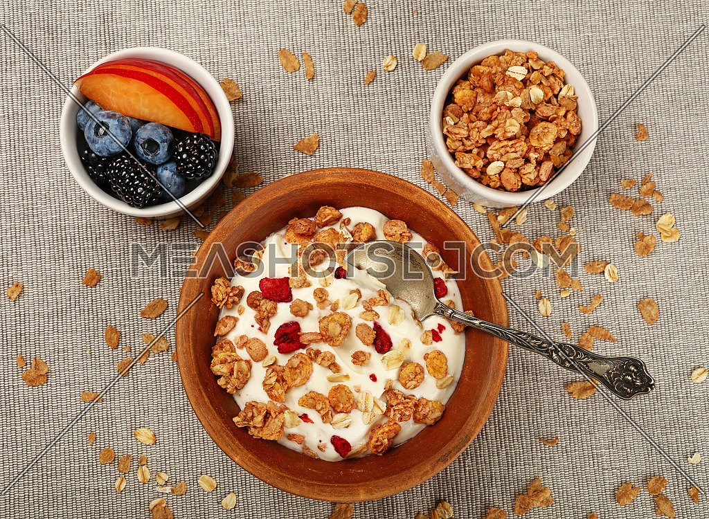 Close up portion of muesli granola breakfast with yogurt, fruits and berries, elevated top view, directly above