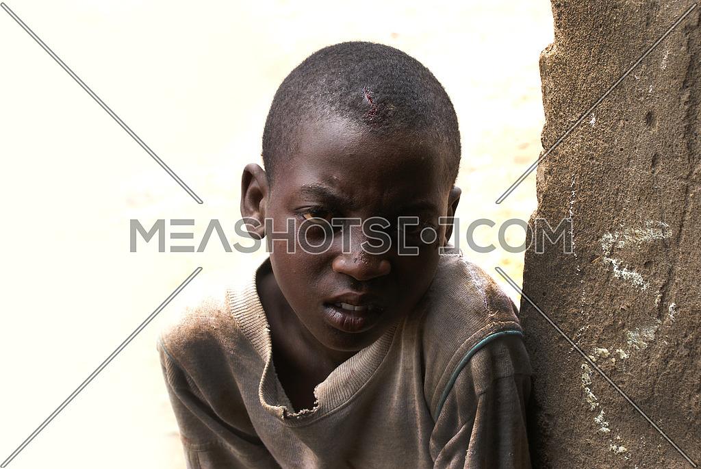 A sad african boy looking towards the camera