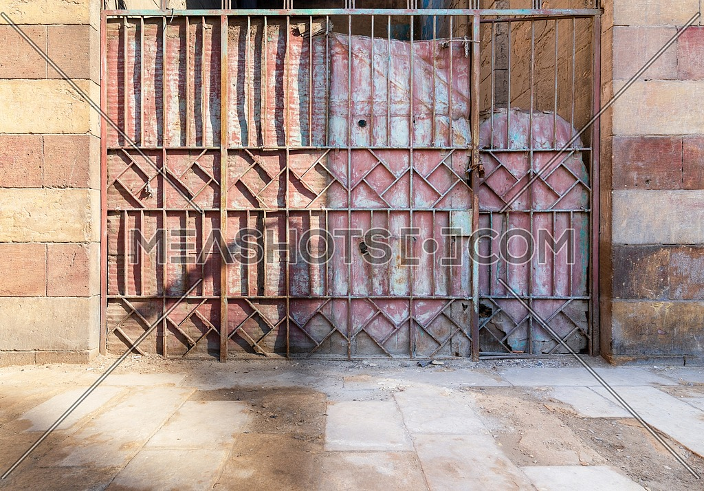 Background of old weathered grunge antique wrought iron gate with geometrical pattern ornaments and sone bricks wall