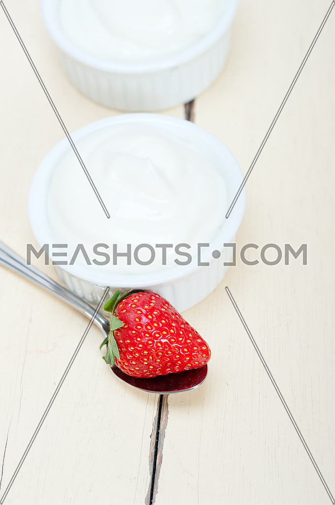 organic Greek yogurt and strawberry over white rustic wood table