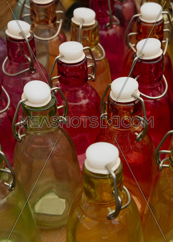 Close up mixed color glass bottles with retro vintage sealing cap on retail display