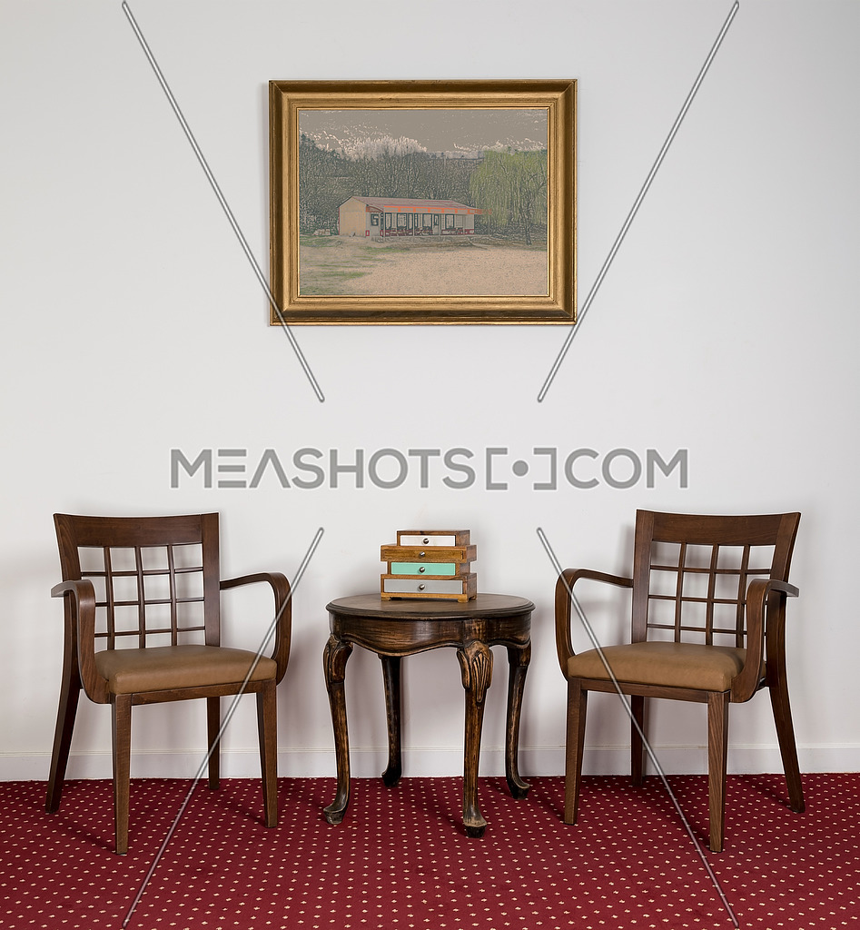 Composition of two wooden armchairs, small round coffee table and framed painting on red carpet and white wall