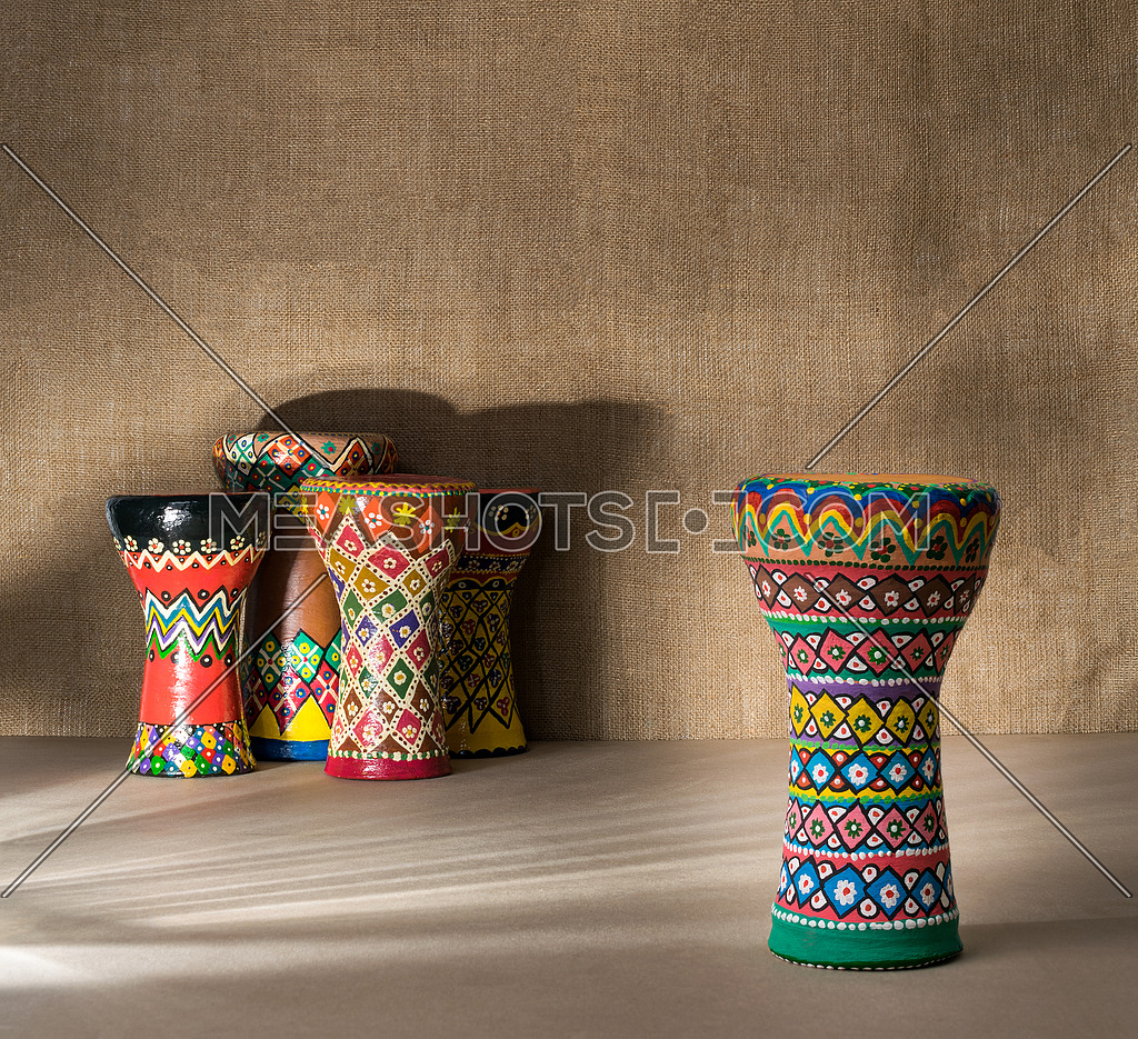Decorated colorful pottery goblet drum on background of goblet drums, wooden table with vanishing shadow lines, and sackcloth wall. Low light shot