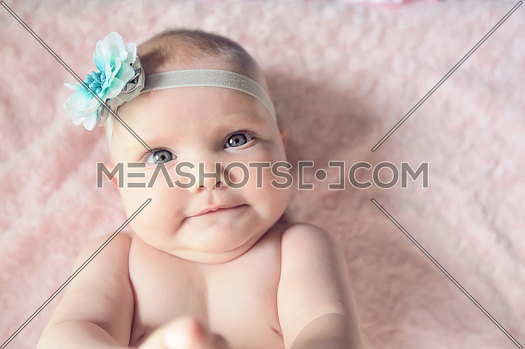 A cute little baby girl on a pink background