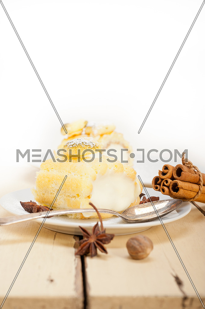 fresh homemade cream roll cake dessert and spices over white rustic wood table