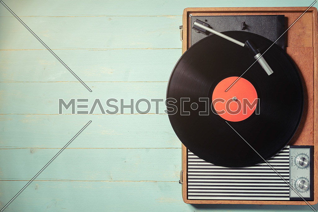 Vintage gramophone with a vinyl record on rustic wooden table, top view and copy space.