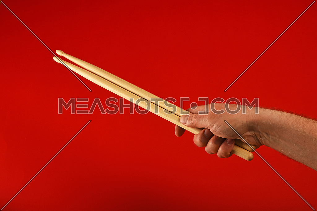 Man hand holding two wooden drumsticks over red background, diagonal