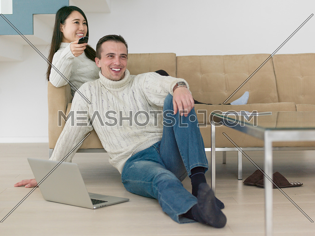 Young multiethnic couple on the sofa watching television together at luxury home