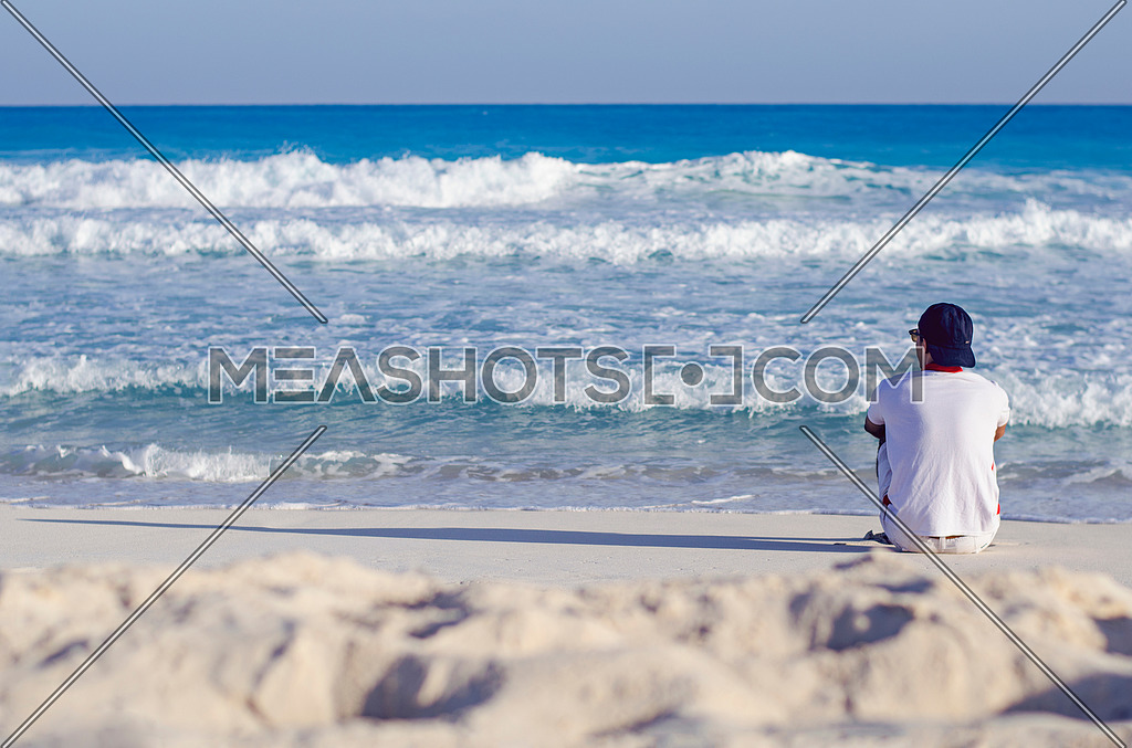 a man sitting alone looking towards the sea