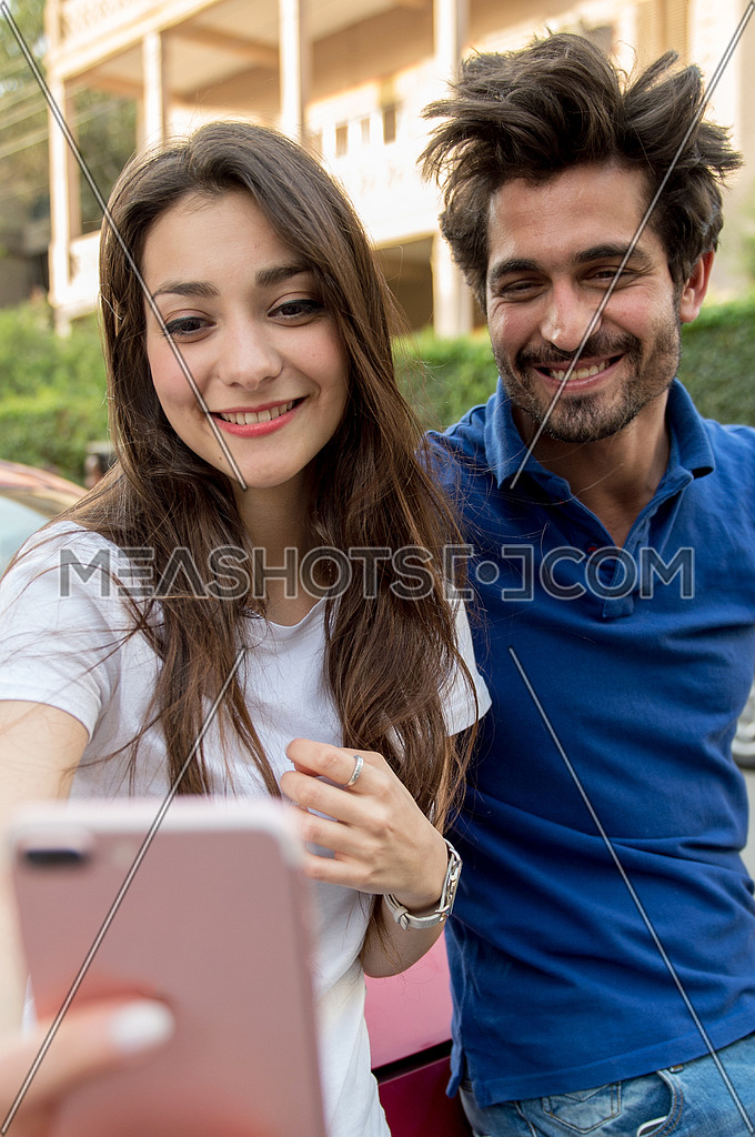 A young man and a young lady take Self portrait on a mobile phone in the street