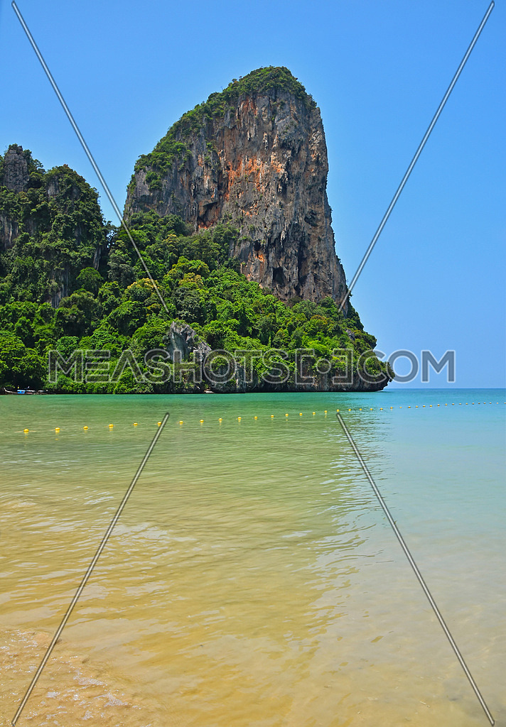 Paradise tropical sunny sand sea beach with sky blue water and forest rock