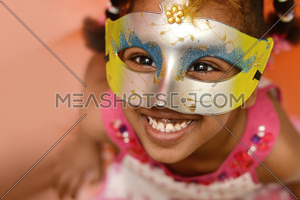 An african little girl wearing a venetian style mask