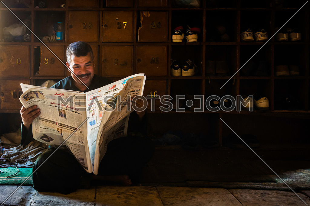 an Egyptian Man smiling while reading a local news paper in the mosque where people put their shoes for prayer