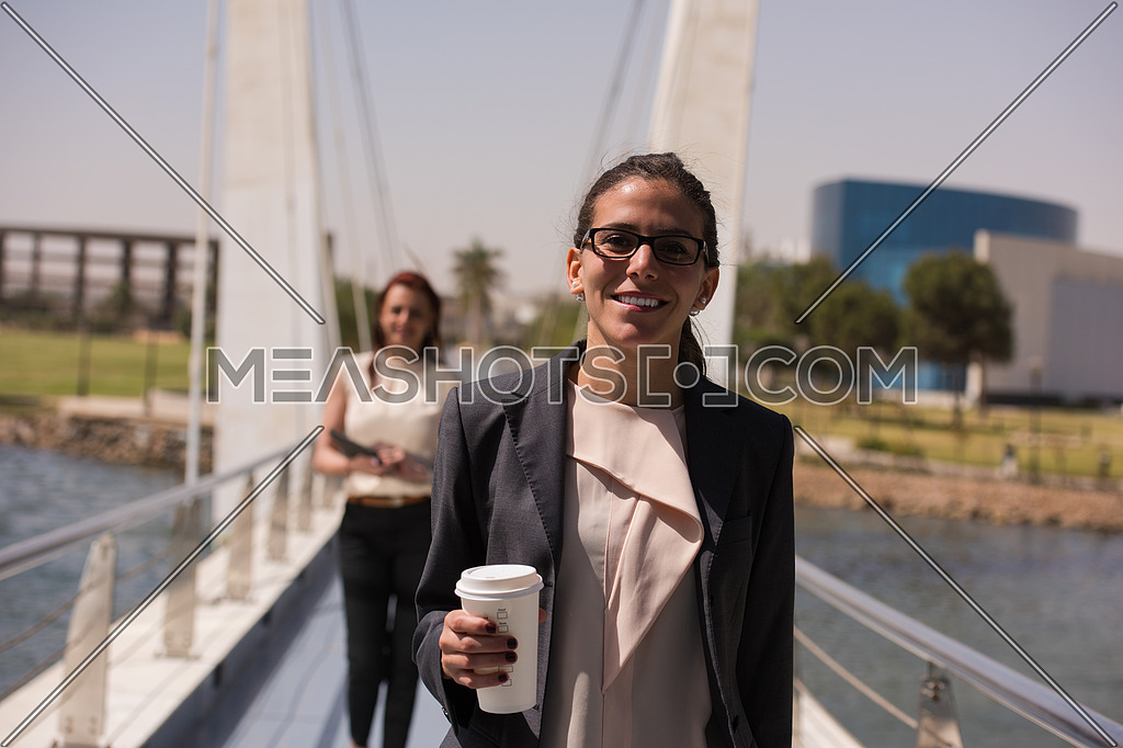 business women walking across a modern footbridge at early mornig while drinking coffee