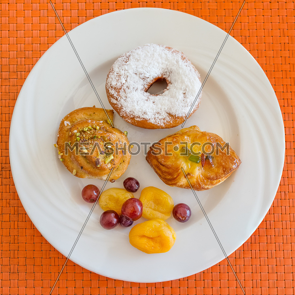In the pictured three pastries served on a white plate with fruits as decoration.