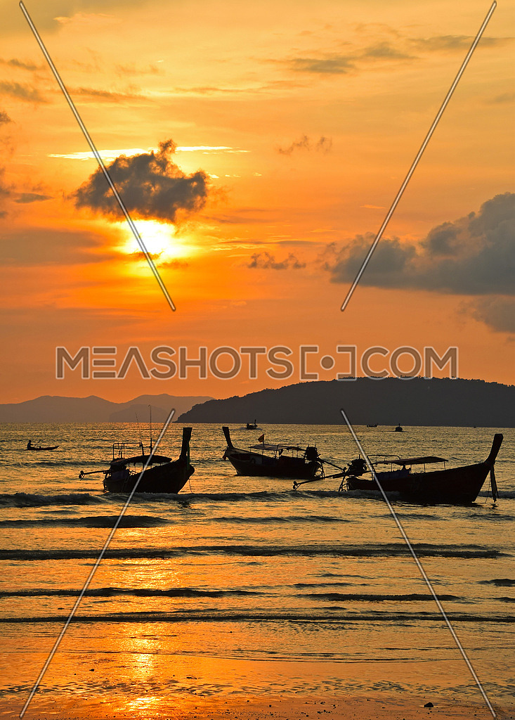 Traditional Thailand long tail boats silhouettes in water near beach during sunset in back light