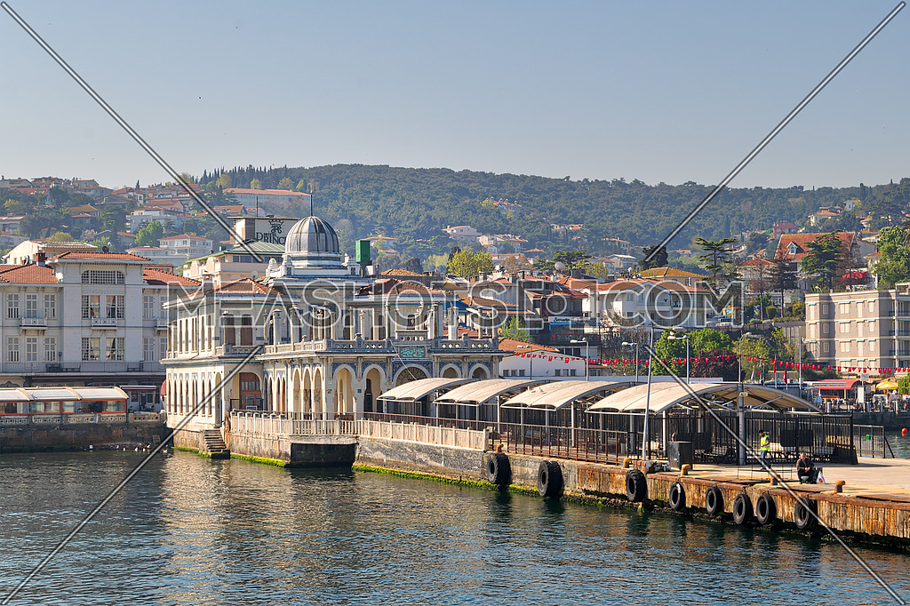 Istanbul, Turkey - April 27, 2017: Buyukada (Princess Island) Ferry Terminal with passengers riding a ferry and summer houses, and green mountains in the background, Istanbul, Turkey