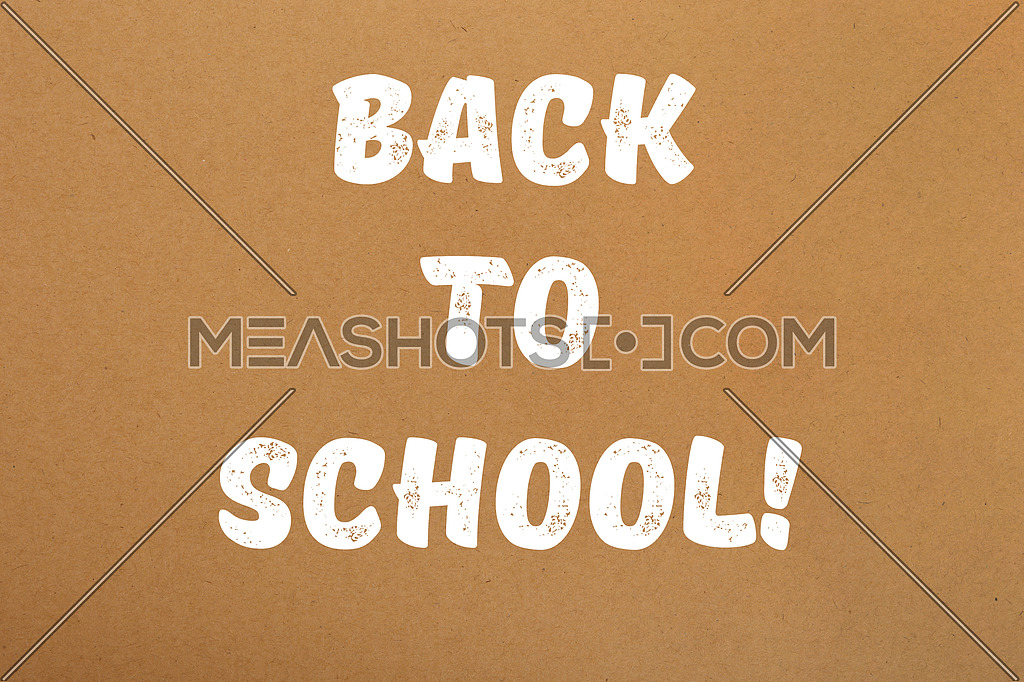 Back to school white paint handwritten sign over brown parchment paper background with copy space