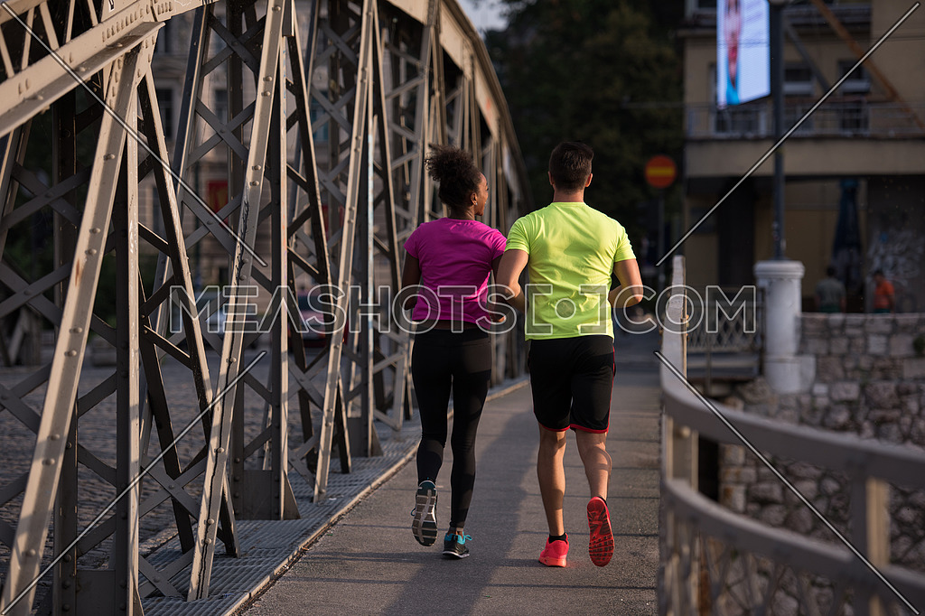 healthy young multiethnic couple jogging across the bridge in the city at early morning with sunrise in background