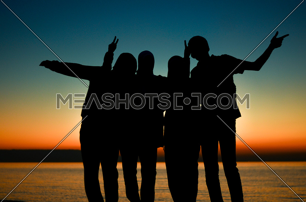 A Four group of friends enjoying their time and having fun , making memories by the beach at sunrise time