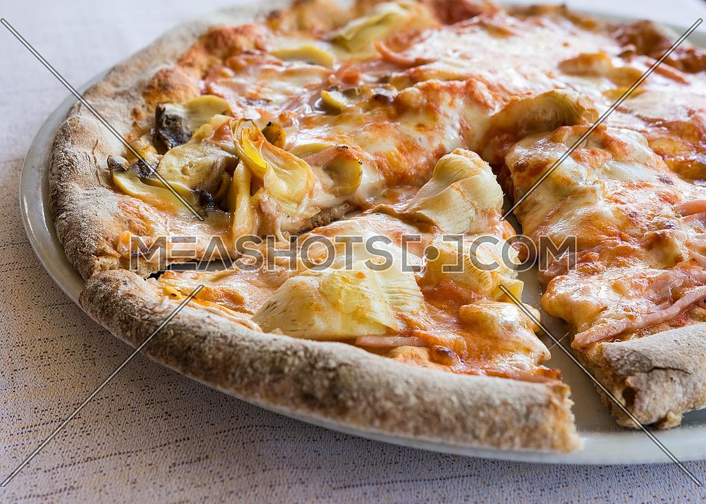 In the pictured a cut pizza with tomato, mozzarella, mushrooms, ham and artichokes.