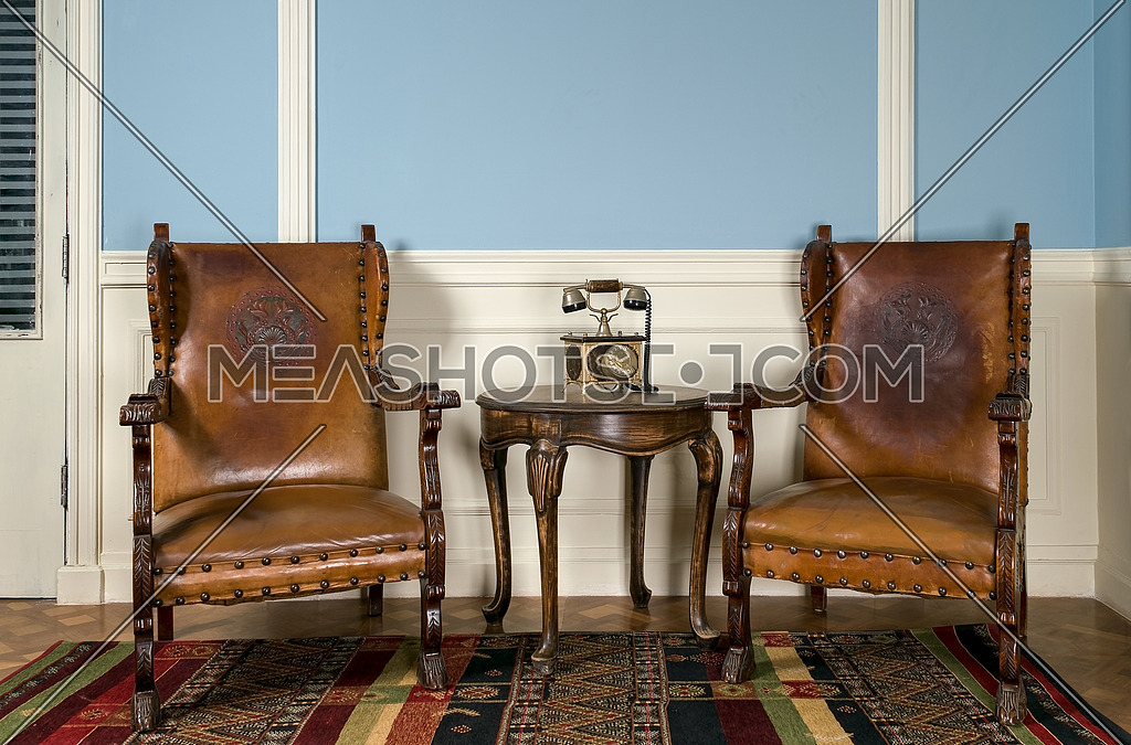 Composition of two wooden retro armchairs and an old analog telephone on small round coffee table on ornate colorful carpet