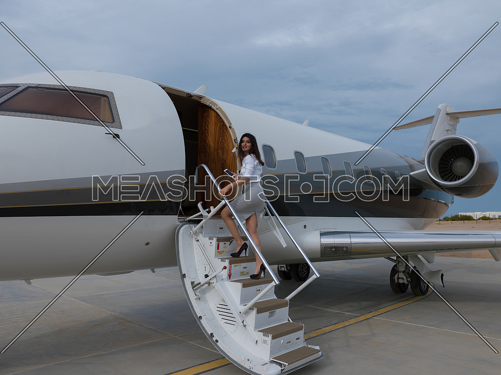 portrait of a young middle eastern businesswoman at the entrance to her private plane