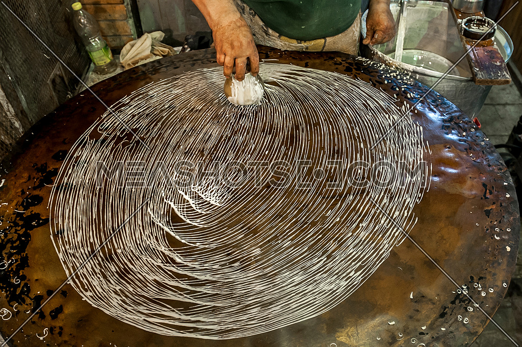 A man preparing kunafa the traditional way on a hot plate   مظاهر شهر رمضان المبارك