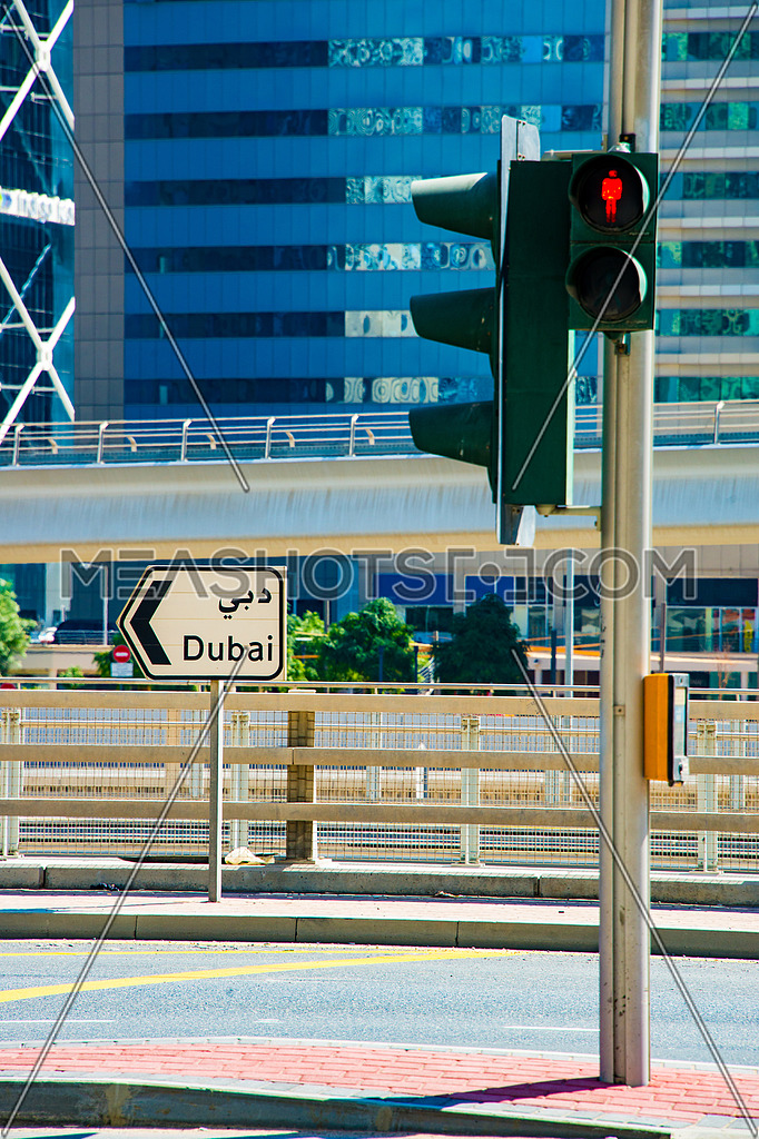 A street sign written on it Dubaiat a traffic intersection