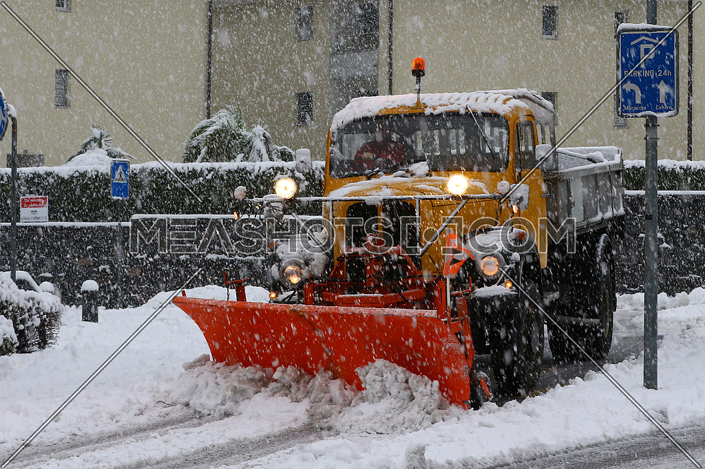 Old snowplow at work clearing city streets during a heavy snow storm