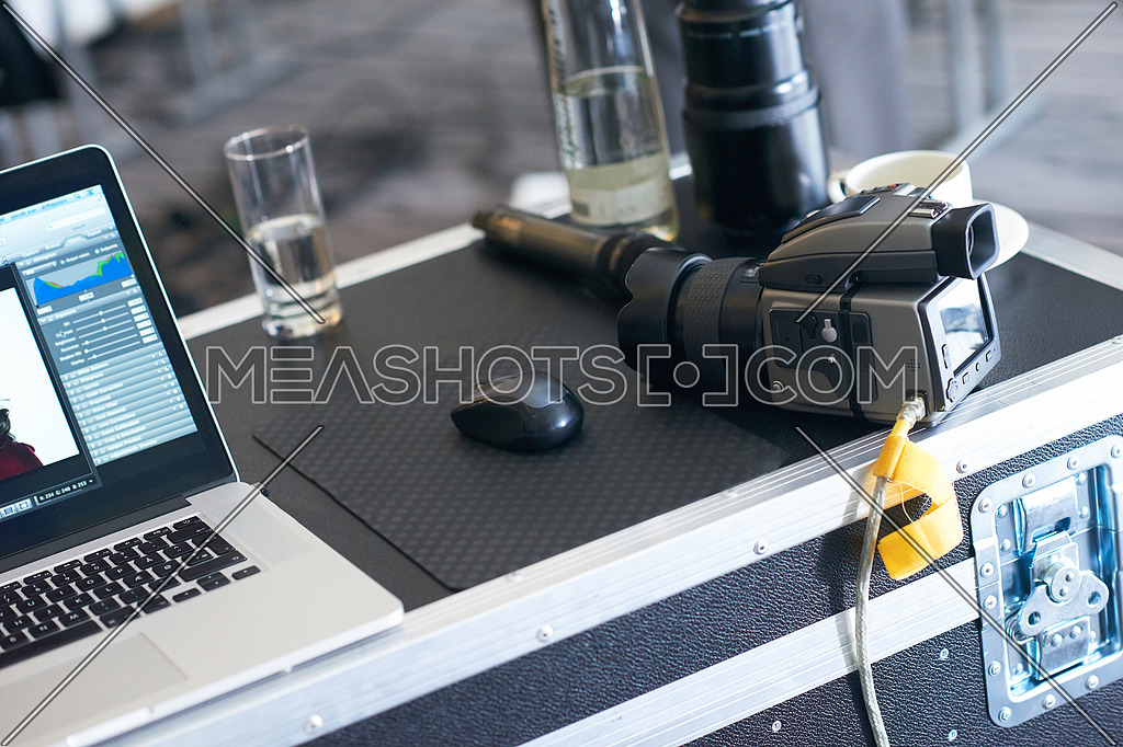 medium format professional photo camera connected to laptop computer in photography studio