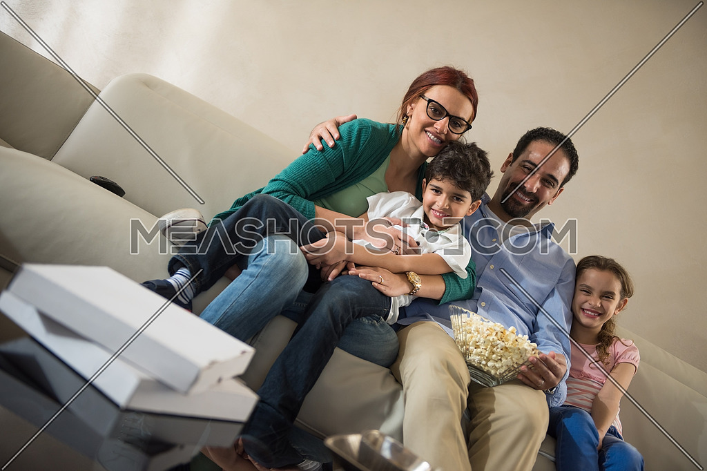 happy middle eastern family enjoys spending a quality time with the kids on the sofa with movies and popcorn