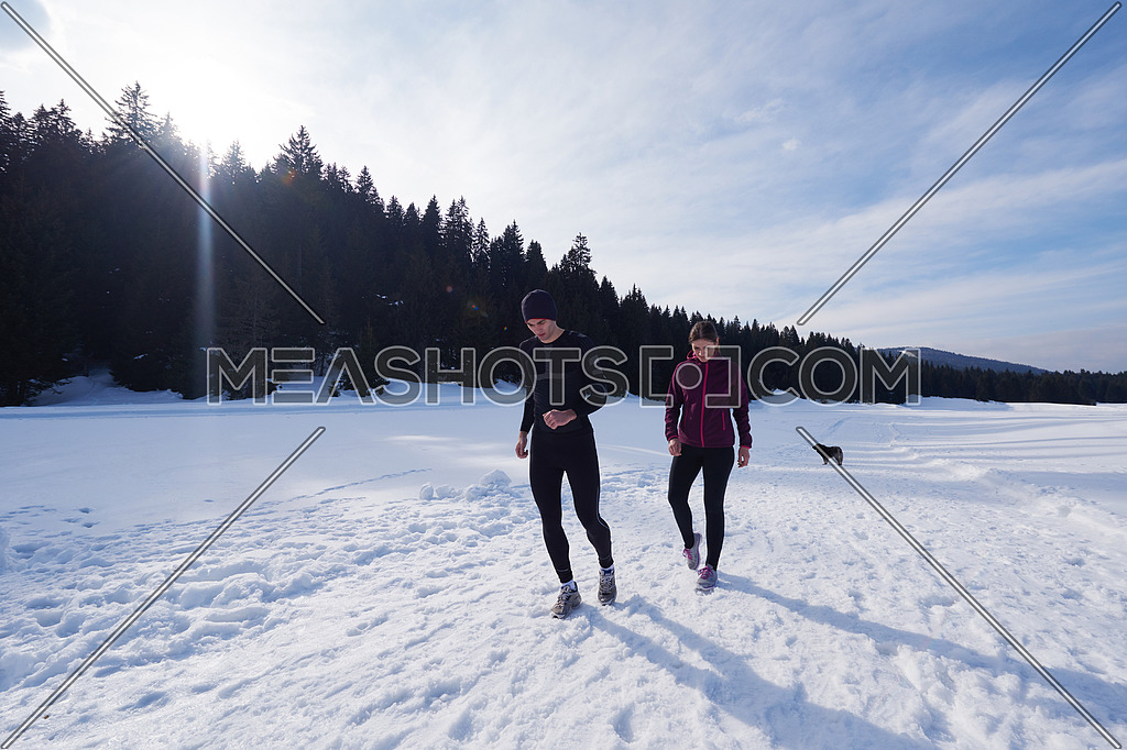 healthy young couple jogging outside on snow in forest. athlete running on beautiful sunny winter day