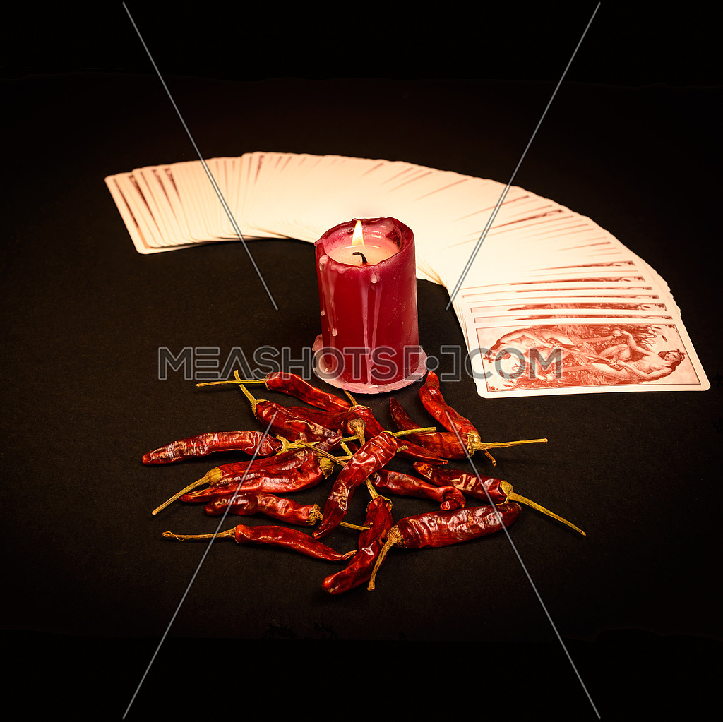 In the pictured a deck of cards open fan , a red candle and red pepper dry.