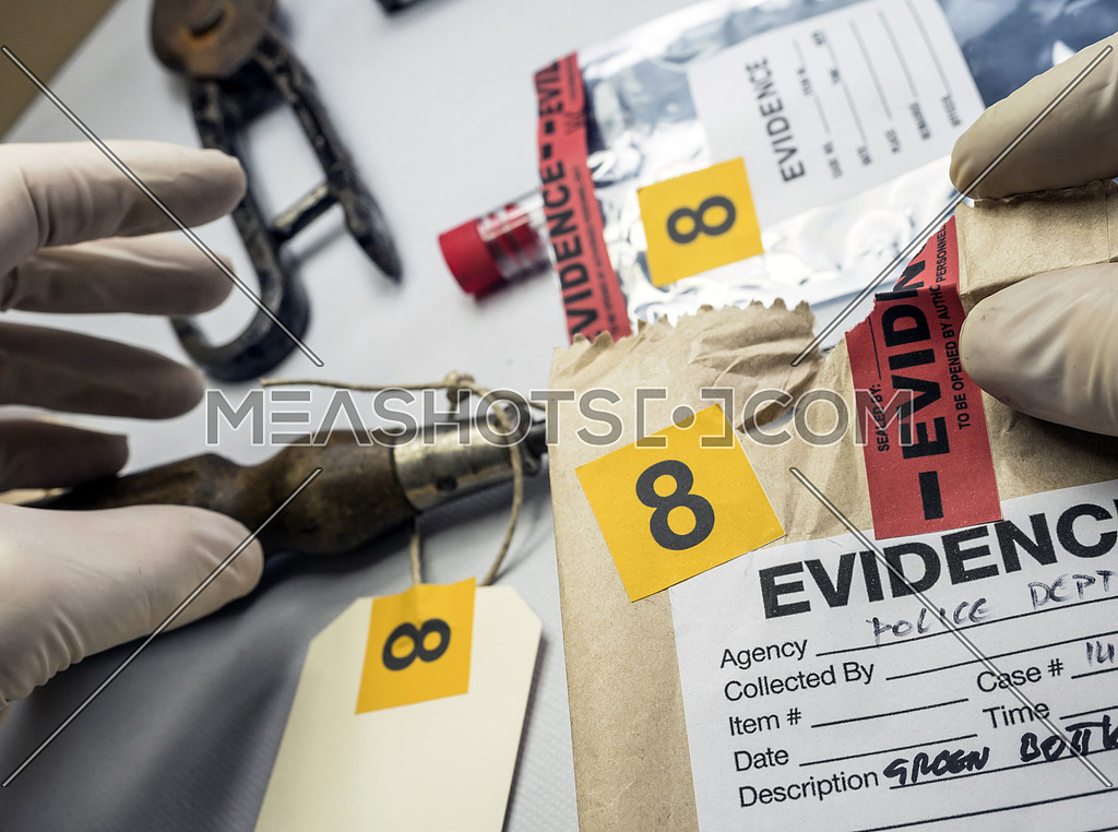 Police expert inspects a screwdriver from the scene of a crime, conceptual image