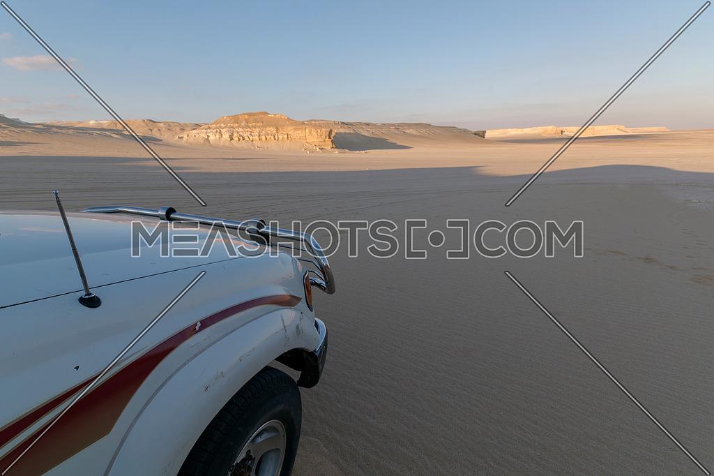 Desert Safari 4*4 white car in Nature Reserve Desert Dunes landscape with blue sky , Fayoum , Egypt