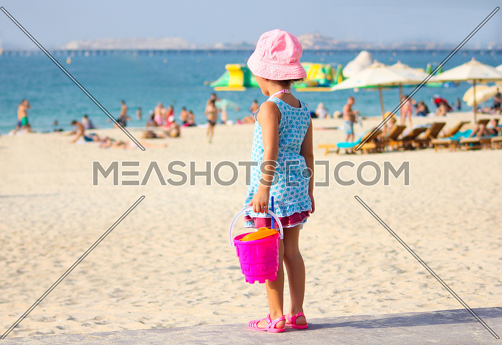 Girl at the beach holding bucket and toys