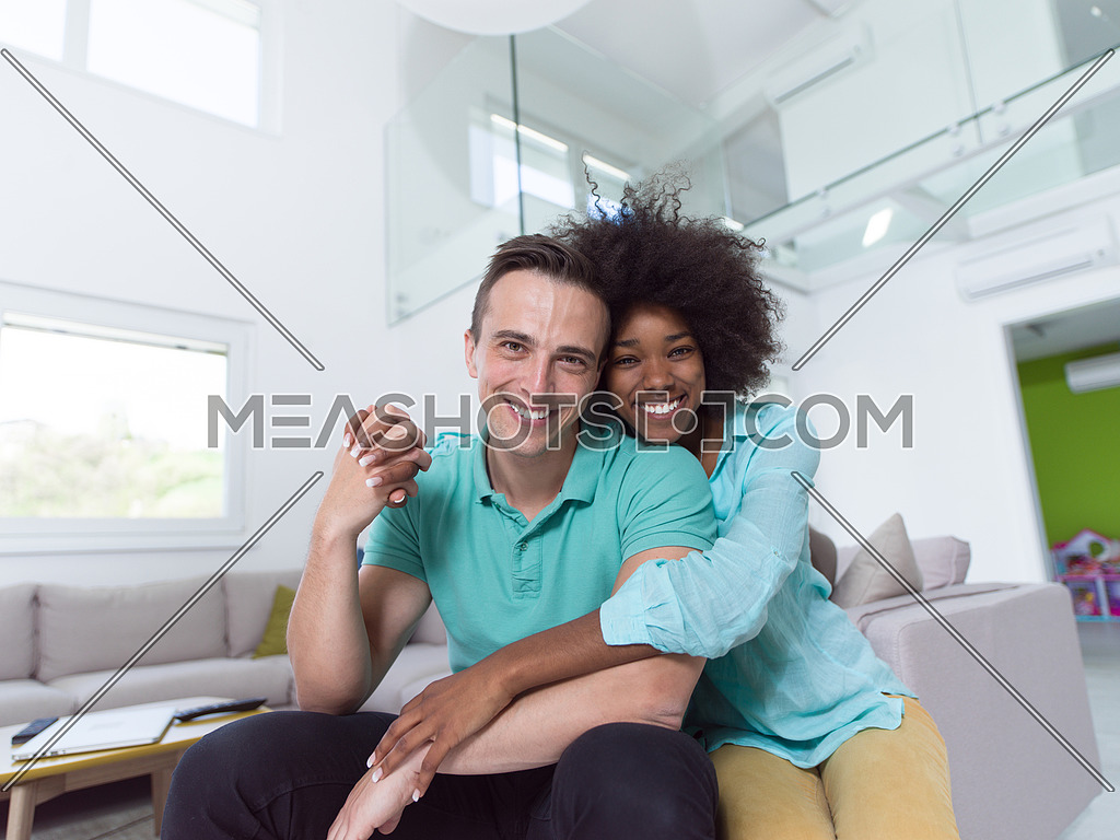 Beautiful young multiethnic couple hugging in their new apartment