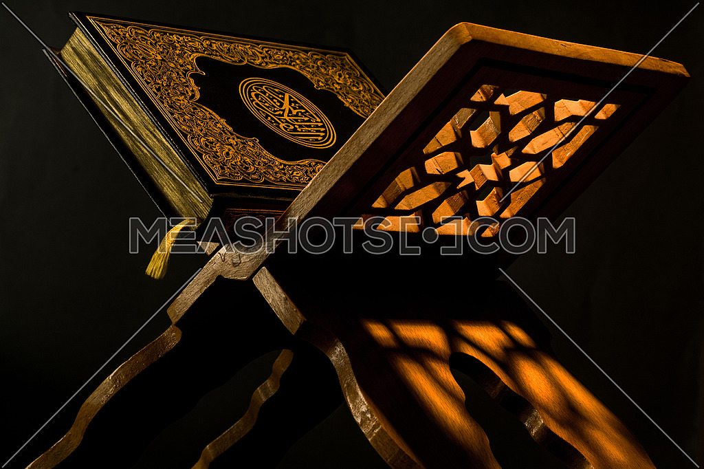 the Quran the holly book of islam placed on a wooden holder