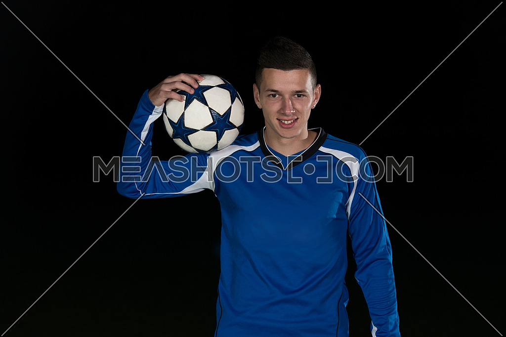 Soccer Player And Ball On Football Stadium Field Isolated On Black Background