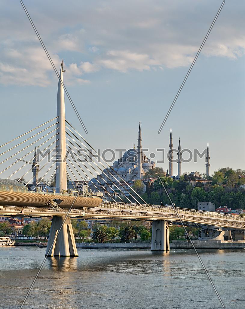 Day shot of Golden Horn Metro Bridge (Halic Bridge) overlapping Suleymaniye Mosque, Istanbul, Turkey