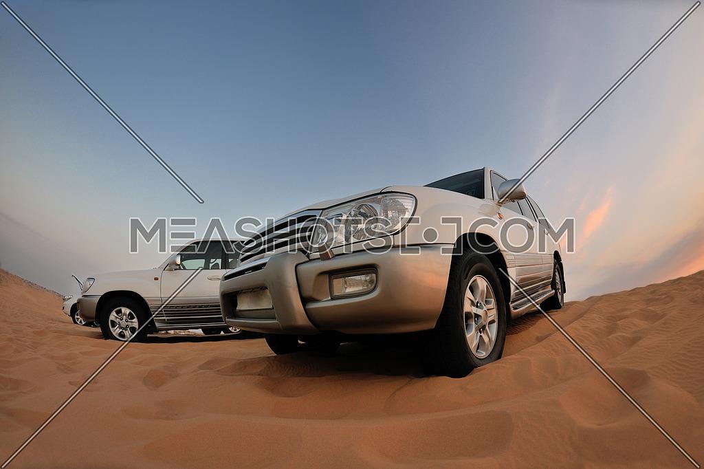 Desert Safari - Off-road jeep vehicles driving in the Arabian Desert at sunset