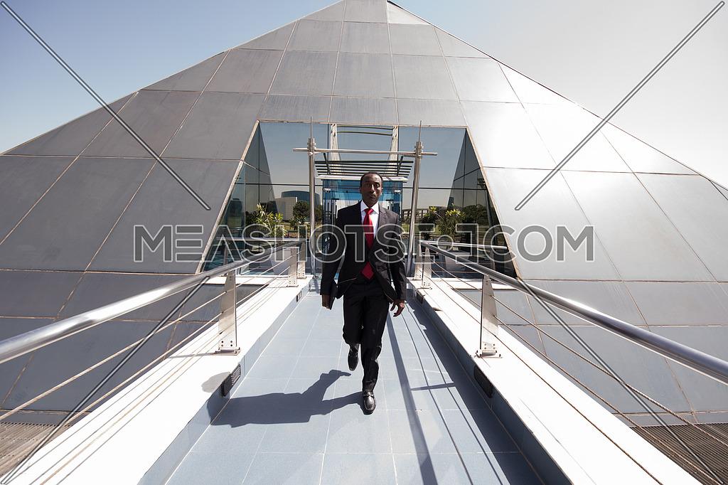 african businessman walking across modern footbridge