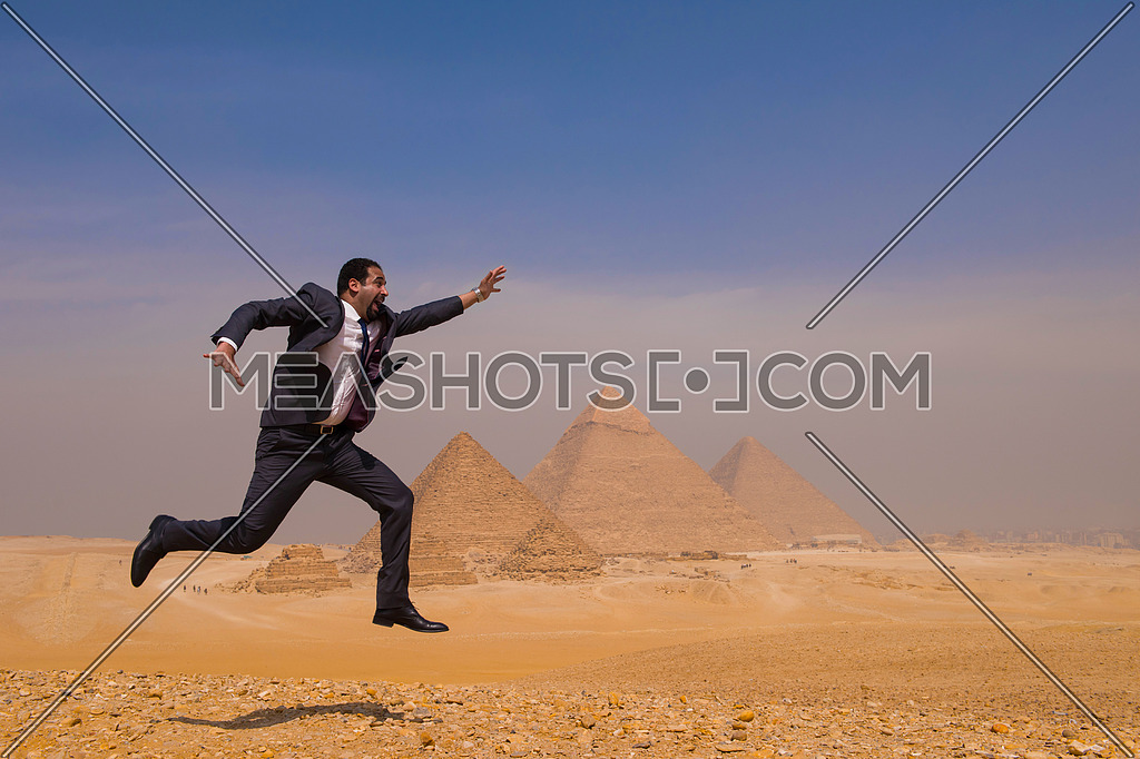 Egyptian business man jumping in desert with pyramids in background