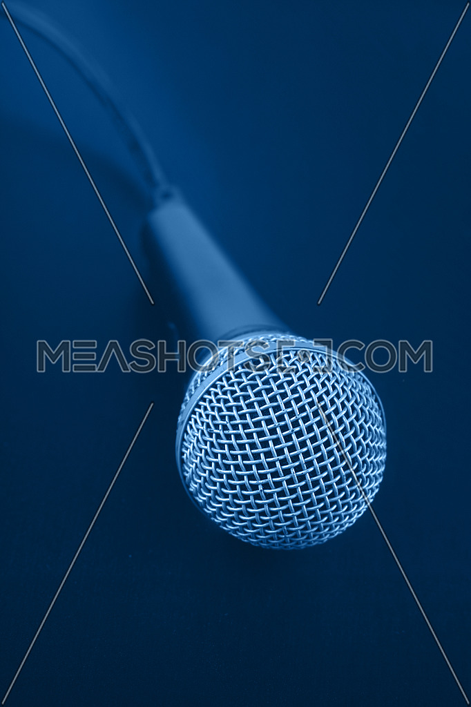 Close up classic wired vocal microphone with cable over dark blue background, high angle view, personal perspective