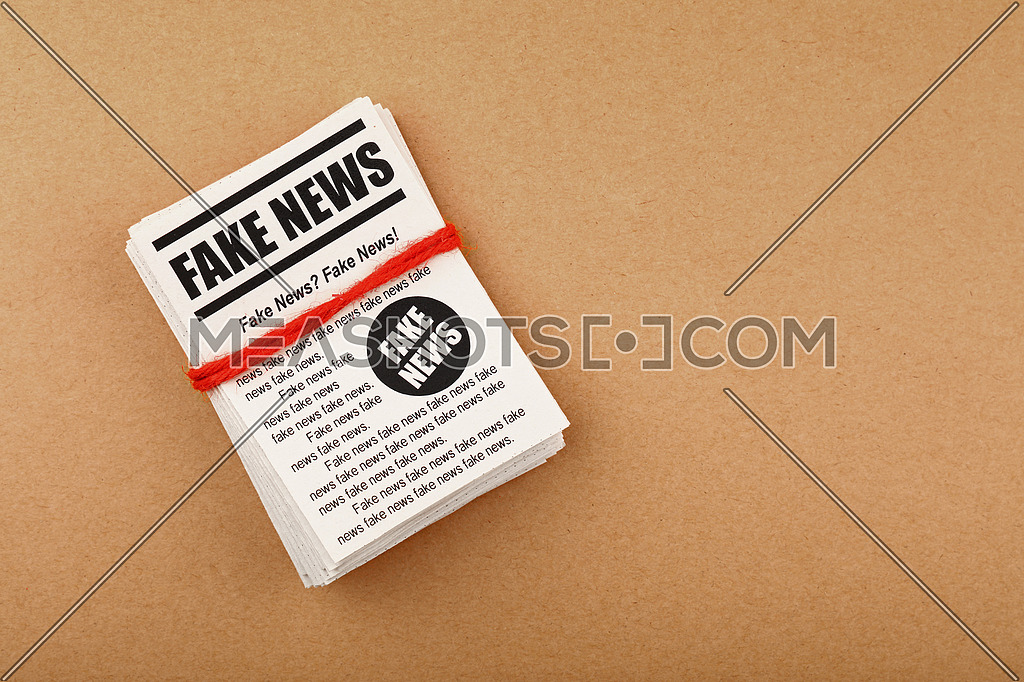 Close up stack of FAKE NEWS newspapers over brown paper background with copy space, elevated top view, directly above
