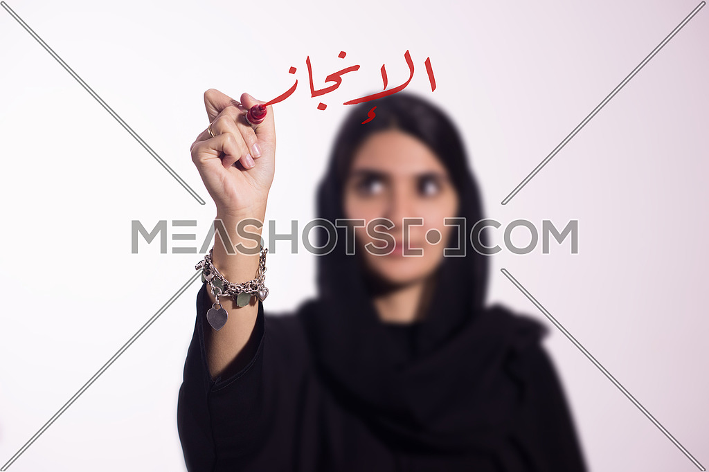 Arabian middle eastern business woman writing with a marker on virtual screen in arabic Achievement  isolated on white background