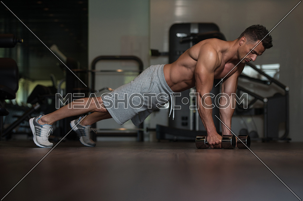 Young Man Doing Push Ups With Dumbbells On Floor-96783
